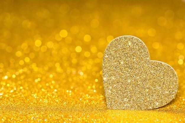 Świecące serce na złotym tle promienistym. brokatowy połysk w kształcie 3d.