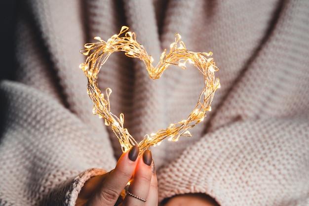 Świecące serce w rękach kobiety. szczęśliwych walentynek. pled, komfort, zimowy, girlandowe serce w rękach kobiety. szczęśliwych walentynek