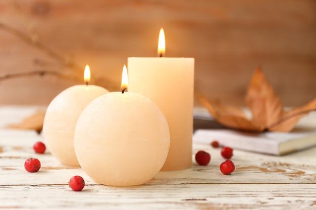 Świecące świece na białym drewnianym stole