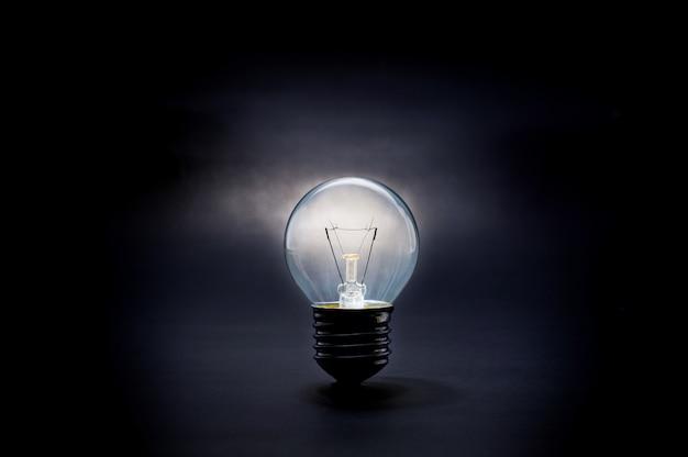 Świecące żarówki w ciemnych pomysłach na inspirację kreatywnością