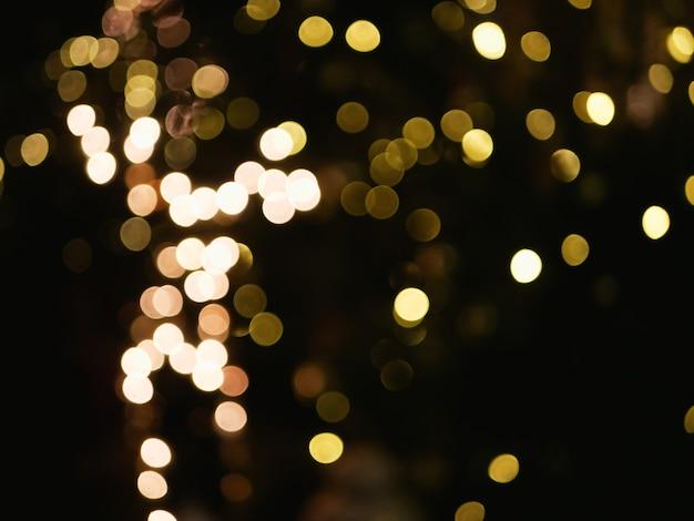 Świecące żółte światła nieostre w ciemności. zdjęcie wysokiej jakości