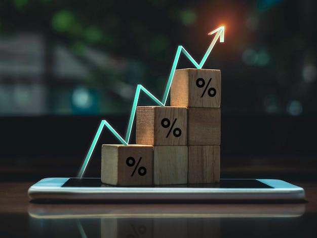 Świecący wznoszący się wskaźnik zygzakowaty, strzałka na drewnianych blokach wykresu kroków z ikonami procentowymi na smartfonie na stole, proces rozwoju biznesu i koncepcja poprawy gospodarczej.