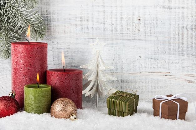 Świece bożonarodzeniowe i noworoczne, pudełka na prezenty i ozdoby świąteczne na śniegu