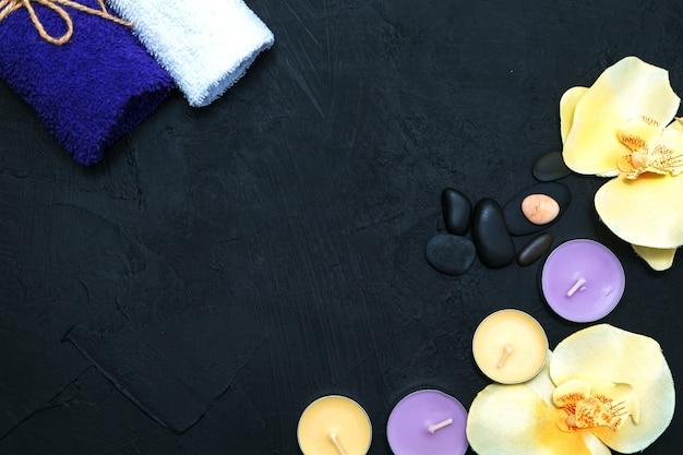Świece, kwiaty orchidei i kamyki na czarnym tle kamienia. widok z góry, miejsce na kopię. koncepcja spa, płaski układ.
