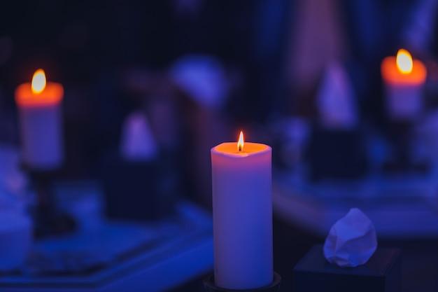 Świece palą się na świeczniku na ciemnym, niebieskawym tle z tyłu