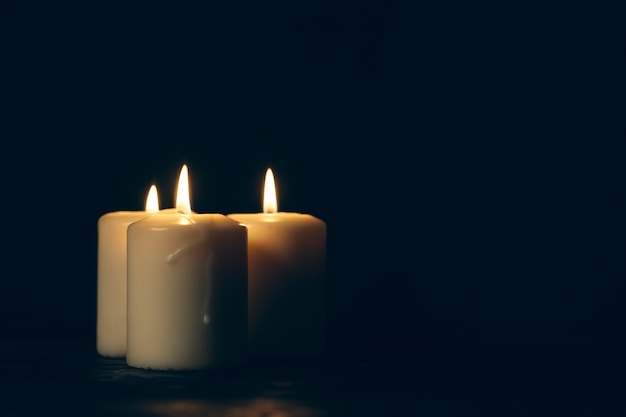 Świece płonące w ciemności nad czernią