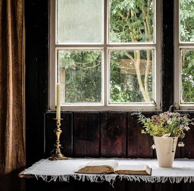 Świecę postawiono obok kwiatów i książkę przed oknem