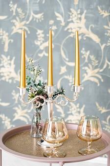 Świece retro w starym stylu i kieliszek do wina na tacy, wystrój domu w stylu vintage na stole, w jasnych kolorach