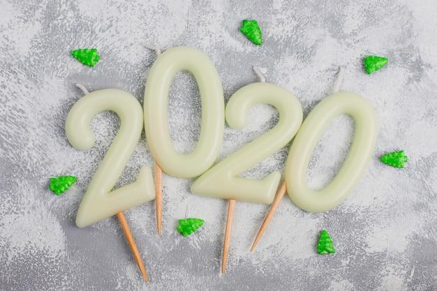 Świece w kształcie liczb 2020 jako symbol nowego roku obok świątecznych świecących świecących cukierków na szarym stole. widok z góry, leżał płasko
