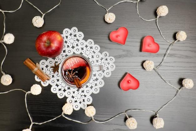 Świece w kształcie serca. grzane wino z przyprawami na koronkowej serwetce, cynamonem i jabłkiem.