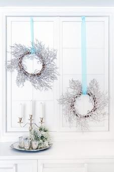 Świece w metalowym świeczniku i świąteczne wieńce.