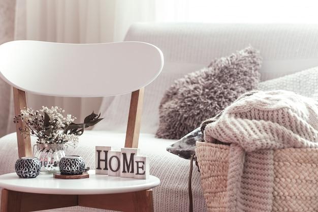 Świece, wazon z kwiatami z drewnianymi literami domu na drewnianym białym krześle. sofa i wiklinowy kosz z poduszkami.