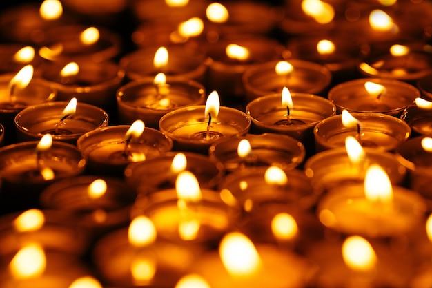 Świece. wiele płonących świec w ciemności. żółte świeczki na czarnym tle.