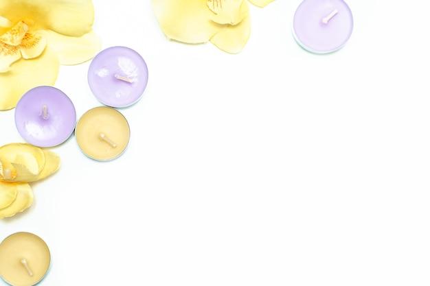 Świece zapachowe i kwiaty orchidei na białym tle. widok z góry, miejsce na kopię. koncepcja spa, płaski układ.
