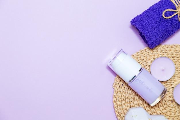 Świece zapachowe, ręcznik, balsam i kamyki na liliowym tle. widok z góry, kopia przestrzeń, układ płaski. koncepcja pielęgnacji spa i ciała.