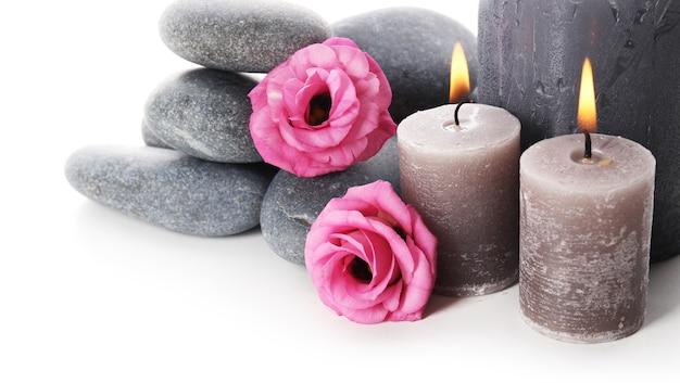 Świece zapachowe z kamyczkami i kwiatem na białym tle