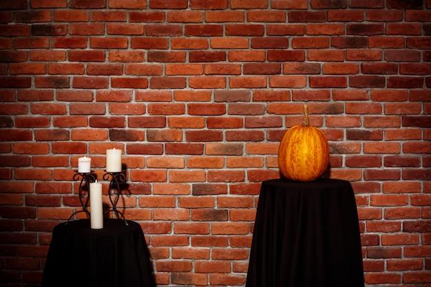 Świeczki i bania na stole nad ściana z cegieł. halloween skopiuj miejsce