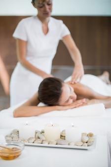 Świeczki i otoczaki w tacy podczas gdy kobieta i masażysta w tle
