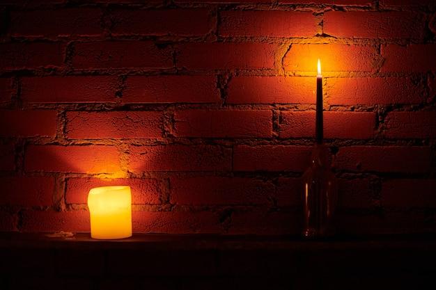 Świeczki na tle ściany na poddaszu. żółty i czerwony ogień w woskowych świecach