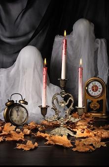 Świeczki wśród opadłych liści z zegarem i duchami