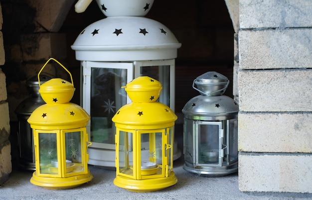 Świecznik w kształcie latarni. żółte i białe świeczniki wykonane z metalu.