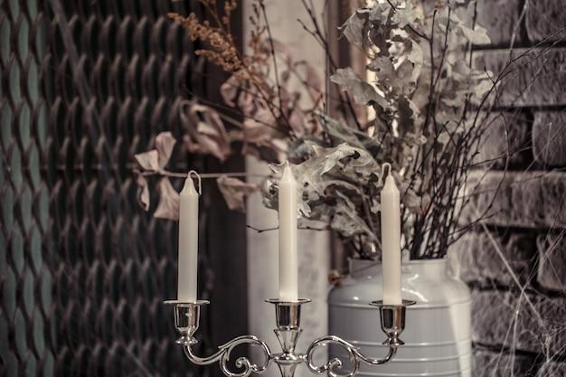 Świecznik ze świecami i wysuszonymi kwiatami