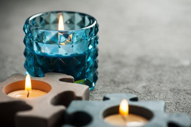 Świeczniki z płonącymi świeczkami na kamiennym tle