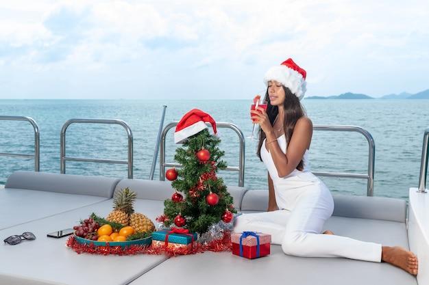 Świerk na jachcie. nowy rok na wyspach. atrakcyjna dama świętuje boże narodzenie w czapce mikołaja na jachcie.