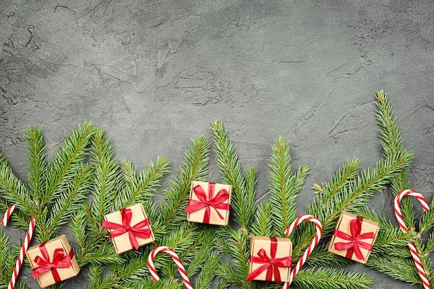 Świerkowe gałęzie, prezenty i trzcina cukrowa na szarym betonowym tle