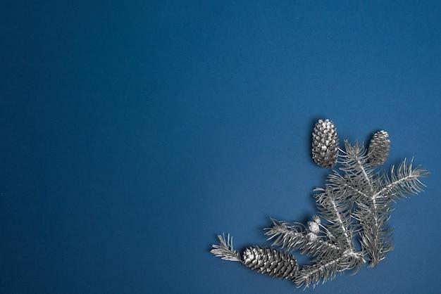 Świerkowe gałęzie są srebrne i świerkowe szyszki na niebieskim tle.