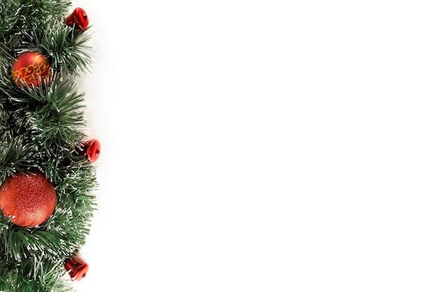Świerkowe gałęzie z czerwonymi świątecznymi zabawkami na białym tle. dekoracje na boże narodzenie 2021.