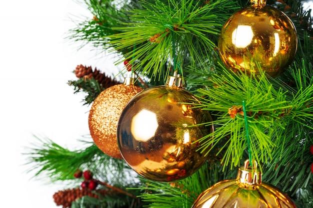 Świerkowe gałęzie ze złotymi bombkami na białym tle