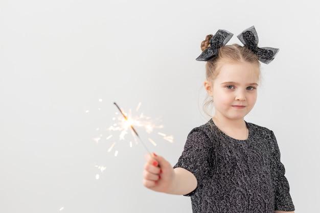Święta, boże narodzenie i nowy rok koncepcja - szczęśliwe dziecko trzyma płonący brylant w dłoni na białym tle z miejsca na kopię.