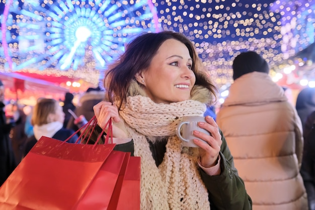 Święta bożego narodzenia i nowego roku, szczęśliwa dojrzała piękna kobieta z torby na zakupy i kubek gorącego napoju na jarmarku bożonarodzeniowym