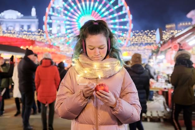 Święta bożego narodzenia i nowego roku, szczęśliwa dziewczyna pisze na czerwonym tekście świątecznej piłki 2021 na jarmarku bożonarodzeniowym