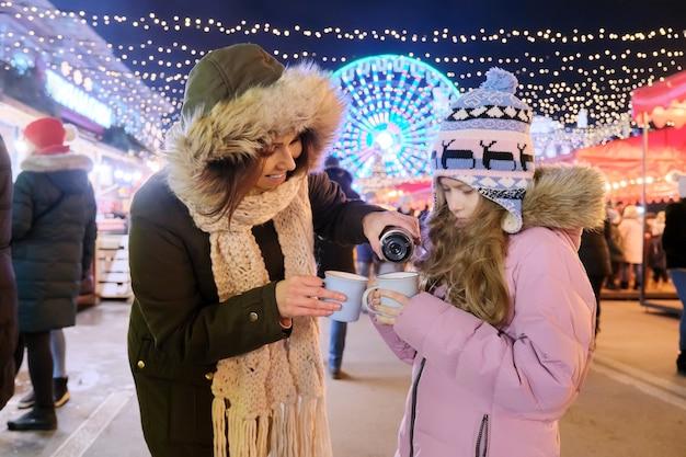 Święta bożego narodzenia i nowego roku, szczęśliwa mama i córka razem idą pijąc gorącą herbatę z kubka na jarmark bożonarodzeniowy
