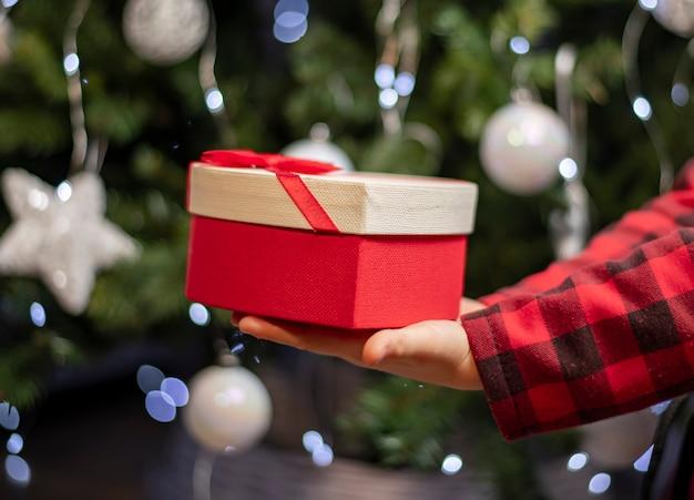 Święta bożego narodzenia i nowy rok, prezent w ręce na tle choinki
