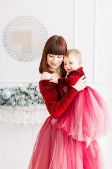 Święta bożego narodzenia i szczęśliwego nowego roku. mama trzyma i przytula jej śliczną córeczkę