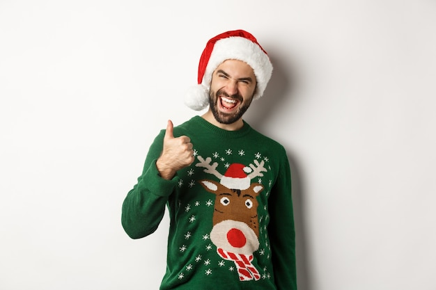 Święta bożego narodzenia, koncepcja uroczystości i partii. mężczyzna cieszy się nowy rok, pokazując kciuk do góry w aprobacie, ubrany w santa hat, białe tło.