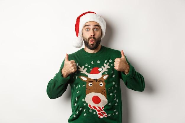 Święta bożego narodzenia, koncepcja uroczystości i partii. zdumiony młody mężczyzna w czapce i swetrze świętego mikołaja, pokazując kciuk z aprobatą, jak coś, białe tło