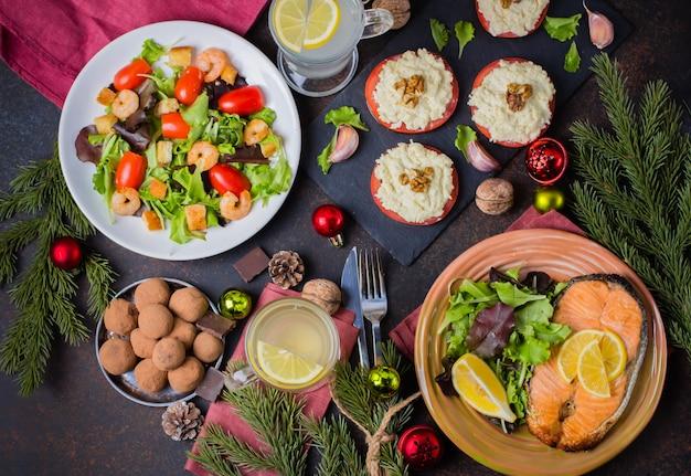 Święta bożego narodzenia lub nowy rok rodzinna koncepcja ustawienia stołu z dekoracją świąteczną. pyszny pieczony stek łosoś, sałatka, przekąski i deser na kamiennym ciemnym stole. widok z góry
