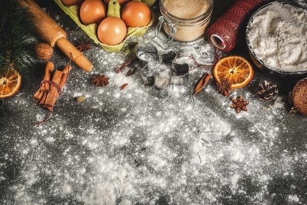 Święta bożego narodzenia, nowy rok, scena kulinarna. składniki, przyprawy, suszone pomarańcze i formy do pieczenia, ozdoby świąteczne (piłki, gałąź jodły, szyszki), na czarnym kamiennym stole