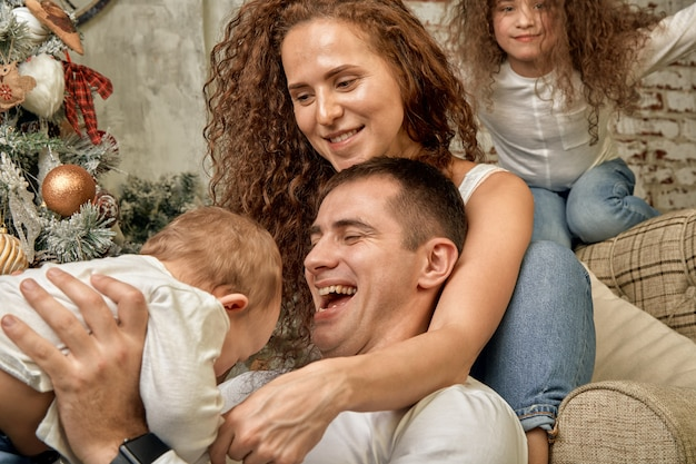 Święta bożego narodzenia. szczęście. portret taty, mamy i dzieci w różnym wieku siedzą na kanapie w domu przy choince i kominku, wszyscy się uśmiechają. szczęśliwego nowego roku