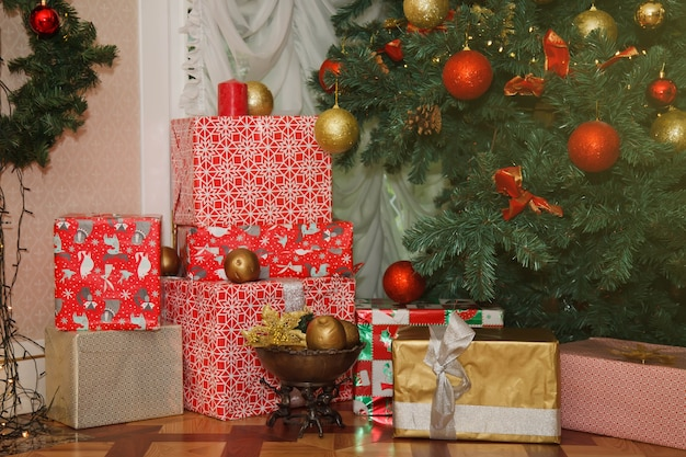 Święta bożego narodzenia tło pudełek z prezentami szczęśliwego nowego roku pod ozdobioną choinką