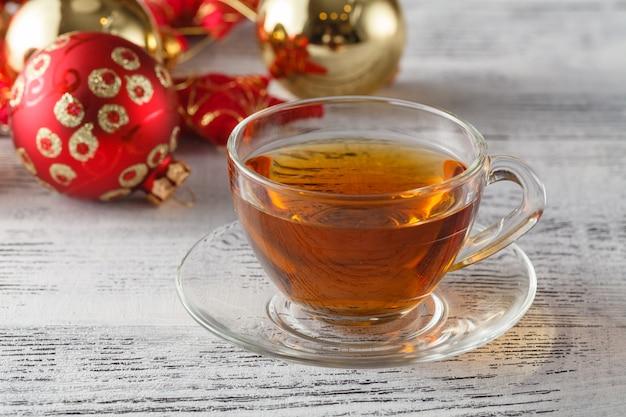 Święta bożego narodzenia tło z filiżanki herbaty, sosny kukurydzy i ozdoby