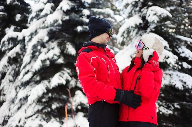 Święta bożego narodzenia w zimowym lesie. portret miłośników nart cieszy się zimą w parku.