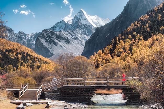 Święta góra chana dorje w jesiennym lesie sosnowym z drewnianym mostem w shangri-la, yading