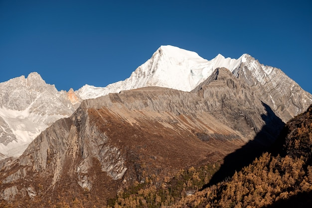 Święta góra ze światłem słonecznym i błękitnym niebem w tybetańskim rezerwacie przyrody yading, daocheng, chiny