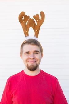 Święta i boże narodzenie koncepcja - młody człowiek szczęśliwy w rogach jelenia na białym tle.