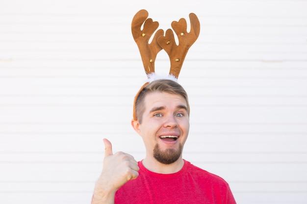 Święta i boże narodzenie koncepcja - młody człowiek w rogach jelenia z kciukiem w górę gestem na białym tle.